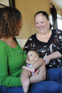 Image of woman breastfeeding with support person smiling at her